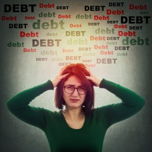 Anxious woman holding her head in both hands with the word 'DEBT' above her